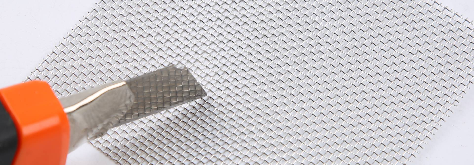 A knife on a sheet of stainless steel window screen mesh.