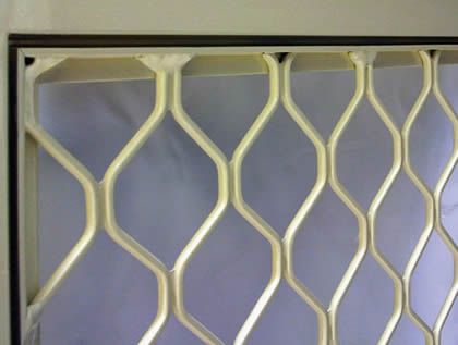 Aluminum diamond grill with silver anodized installed to a window.