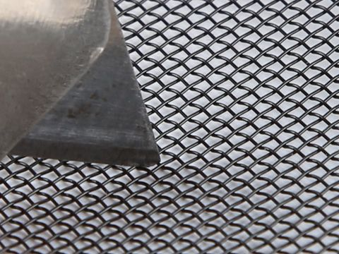 There is a knife resistant mesh being cut by a knife.