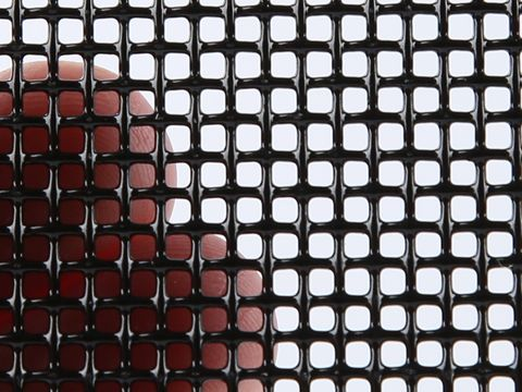 A piece of 11 mesh SS316 security screen in a man's hand.